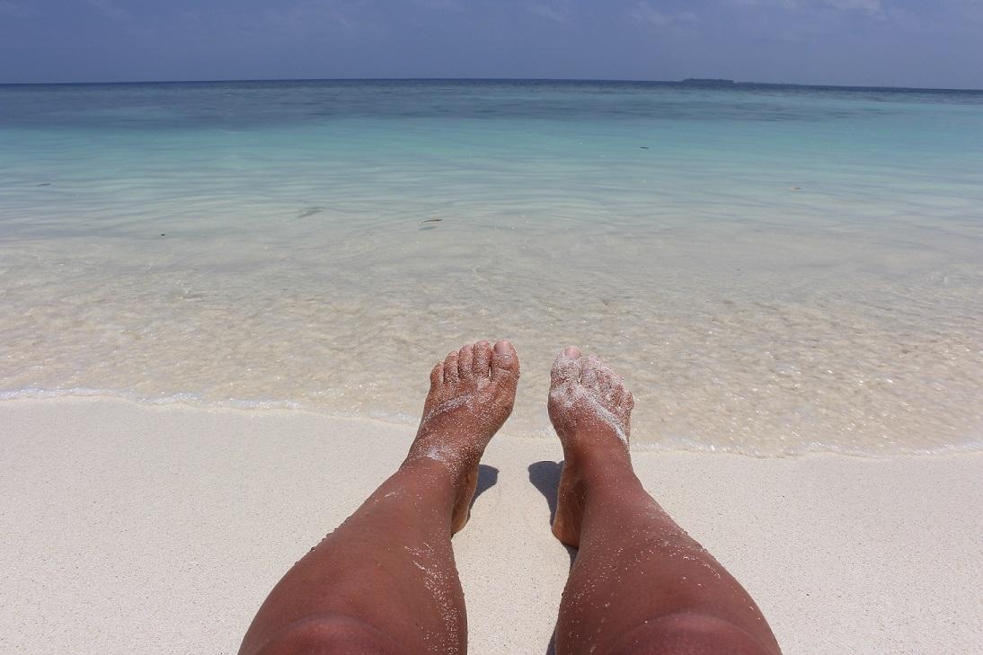 Pés na areia na ilha de Ukulhas