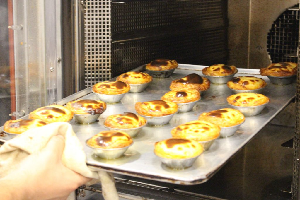 Tabuleiro de pastéis de nata a sair do forno, na Pastelaria Batalha, Lisboa, Portugal